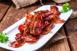 Bacon on White Plate with Herbs